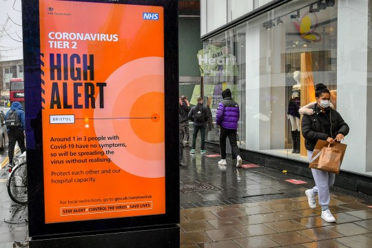 A sign warns shoppers in the centre of Bristol of the tier 2 high alert, as people in Tier 2 areas of coronavirus restrictions continue with their Christmas preparations