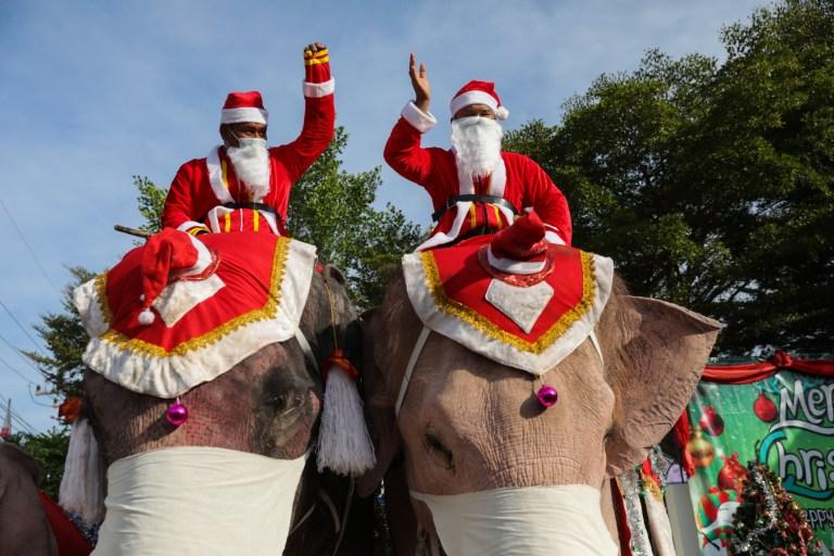 Des formateurs d'éléphants thaïlandais habillés en Père Noël saluent les enfants de l'école primaire Jirasat Wittaya le 23 décembre 2020 à Phra Nakhon si Ayutthaya, Thaïlande.