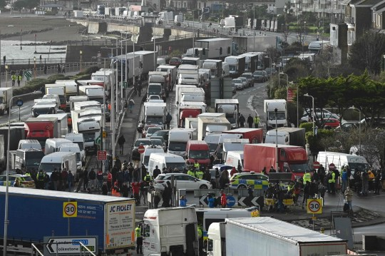 Drivers stand with their HGV freight lorries blocking the entrance trying to enter the port of Dover in Kent, south east England, on December 23, 2020, that is still cordoned after the UK and France agreed a protocol to reopen the border to accompanied freight arriving in France from the UK requiring all lorry drivers to show a negative Covid-19 test. - France and Britain reopened cross-Channel travel on Wednesday after a 48-hour ban to curb the spread of a new coronavirus variant but London has warned it could take days for thousands of trucks blocked around the port of Dover to get moving. (Photo by JUSTIN TALLIS / AFP) (Photo by JUSTIN TALLIS/AFP via Getty Images)