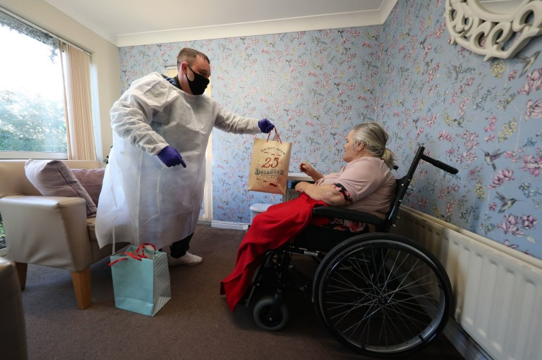 Chris Mills hands a gift to his mother Carol Roberts during a Christmas Day visit at Aspen Hill Village care home in Hunslet, Leeds. The care home is able to host almost 50 visits for family members this Christmas after running successful trials of lateral flow testing for coronavirus. PA Photo. Picture date: Friday December 25, 2020. See PA story HEALTH Coronavirus. Photo credit should read: Danny Lawson/PA Wire