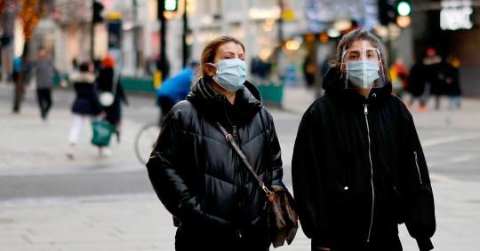 Des piétons portant un masque facial ou une couverture en raison de la pandémie de COVID-19 marchent le long d'une rue calme d'Oxford Street dans le centre de Londres le 22 décembre 2020. - Les emprunts du gouvernement britannique ont continué de grimper en novembre suite à une action d'urgence pour soutenir l'économie touchée par le virus a néanmoins rebondi plus fort que prévu au troisième trimestre, selon les données officielles mardi.  Le mois dernier, les emprunts du gouvernement ont atteint 31,6 milliards de dollars (41,8 milliards de dollars, 34,2 milliards d'euros), un record pour novembre - prenant la dette nette du secteur public à 2,1 billions de dollars, a déclaré le Bureau des statistiques nationales dans un communiqué.  (Photo par Tolga Akmen / AFP) (Photo par TOLGA AKMEN / AFP via Getty Images)