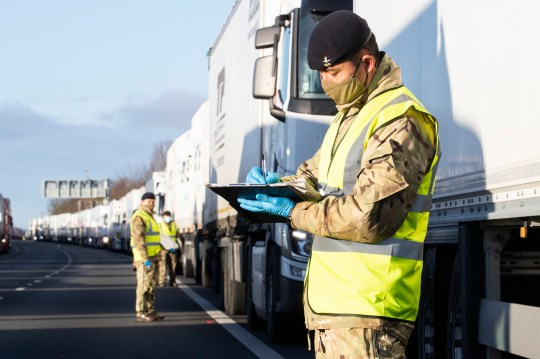 Handout photo issued by the Ministry of Defence (MoD) of a British Army soldiers delivering Covid-19 tests to a lorry drivers on the M20 in Kent. PA Photo. Picture date: Friday December 25, 2020. Delays continue as travellers must be able to show proof of a negative test result carried out within the past 72 hours in order to be able to cross into France. See PA story HEALTH Coronavirus. Photo credit should read: Cpl Nicholas Egan RAF/Ministry of Defence/Crown Copyright/PA Wire NOTE TO EDITORS: This handout photo may only be used in for editorial reporting purposes for the contemporaneous illustration of events, things or the people in the image or facts mentioned in the caption. Reuse of the picture may require further permission from the copyright holder.