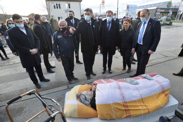 Le Premier ministre croate Andrej Plenkovic, au centre, pointe son doigt alors qu'il se tient à côté d'une femme âgée qui a été évacuée en raison d'un tremblement de terre, à Petrinja, en Croatie, le mardi 29 décembre 2020. Un fort tremblement de terre a frappé la Croatie mardi, avec quelques des blessés signalés ainsi que des dommages considérables aux toits et aux bâtiments au sud-est de la capitale.  (Photo AP)