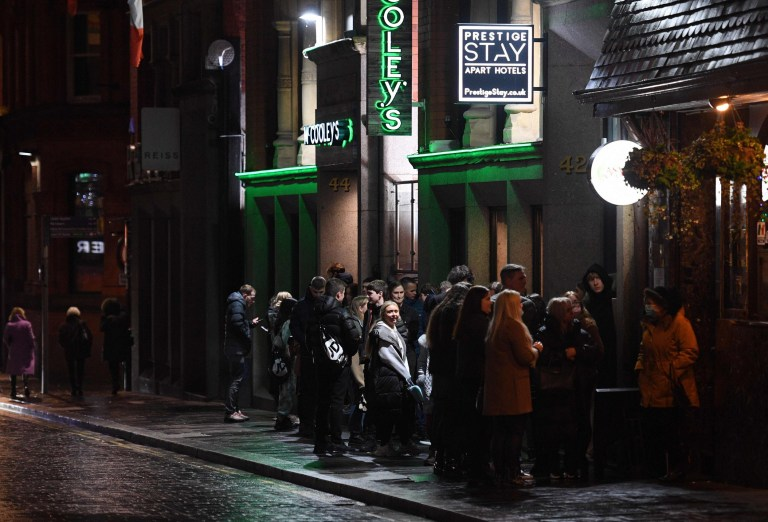 Revellers queue outside a venue in central Liverpool, northwest England