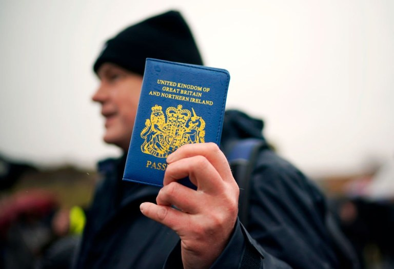 A Vote Leave supporter holds up a blue UK passport in Grangetown, near Sunderland on March 16, 2019