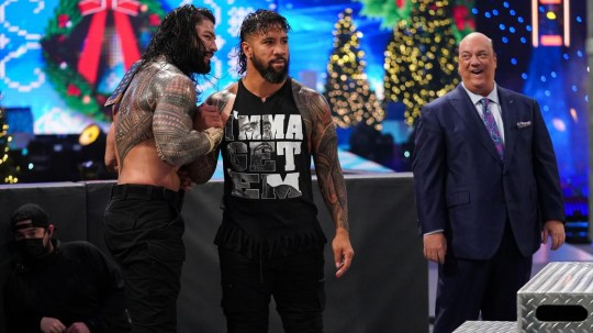 Universal Champion Roman Reigns celebrates with WWE superstar Jey Uso and Paul Heyman after beating Kevin Owens on SmackDown on Christmas Day
