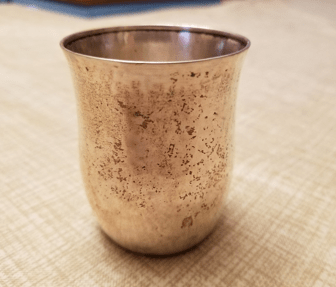 Rust-stained metal cup