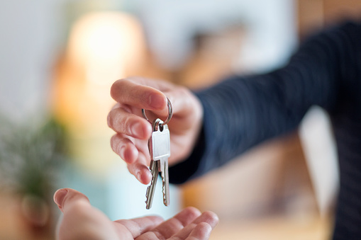 a Close-up of the hand over of house key after someone's bought a new home