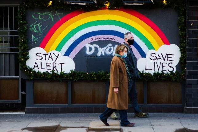 couple wearing face masks walking past rainbow graffiti