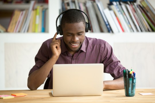 Casual smiling office worker in headphones looking at laptop screen.