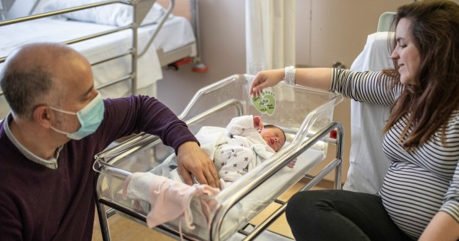 Parents look after their new born baby in a maternity ward