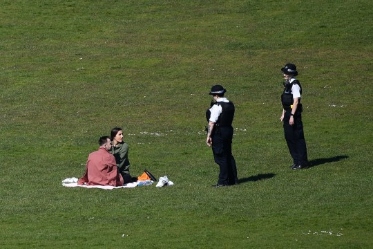 A couple are spoken to by two police officers in Greenwich Park in London on April 5, 2020, as the warm weather tests the nationwide lockdown to combat the novel coronavirus pandemic. - The daily toll of deaths from COVID-19 has been steadily increasing by more than 500 deaths a day this week and the country is bracing for an expected peak in the next week to 10 days. (Photo by Ben STANSALL / AFP) (Photo by BEN STANSALL/AFP via Getty Images)