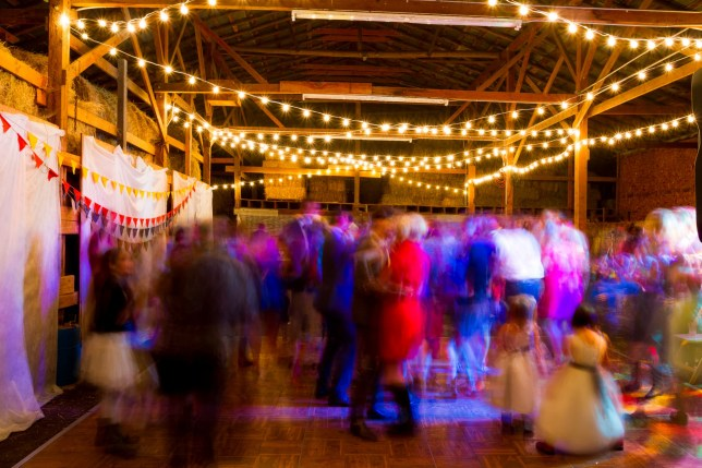 A long slow shutter speed was used to blur the crowd and create a sense of motion at this wedding reception dance party in an old barn in Oregon at night.