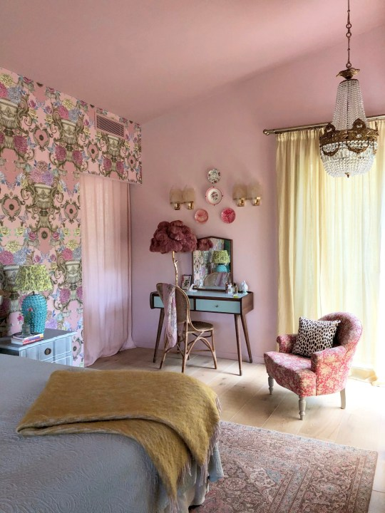 Pink bedroom with patterned pink statement wall, small pink chair, pale blue dressing table and yellow blanket on the bed. Matthew Williamson.
