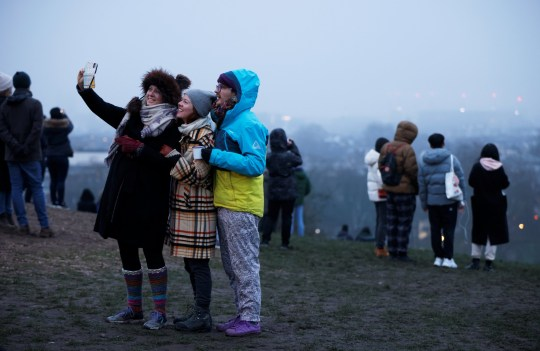 People take selfies at dawn on the first day of 2021 on Primrose Hill amid the coronavirus disease (COVID-19) outbreak, in London, Britain January 1, 2021. REUTERS/John Sibley