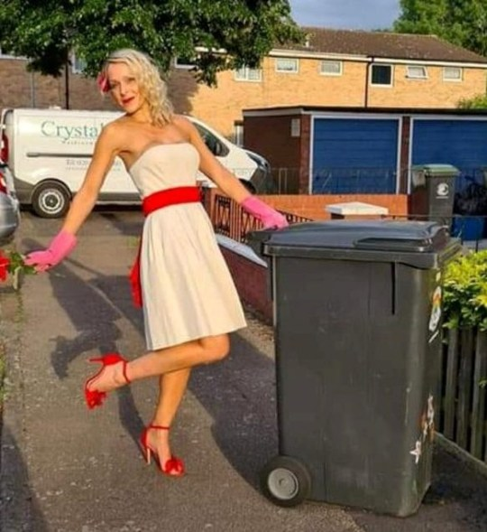 nicola wearing white dress with red accessories next to wheelie bin