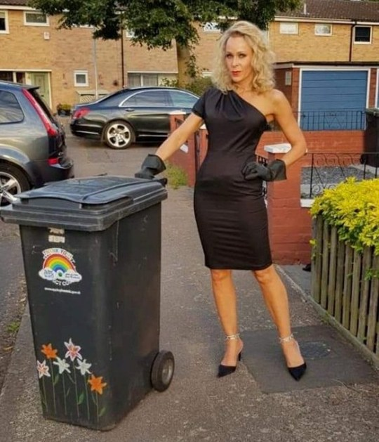 nicola matthews wearing a black dress with matching gloves to take out the bins