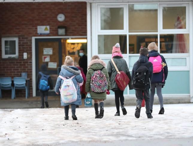 Five young pupils arrive at school