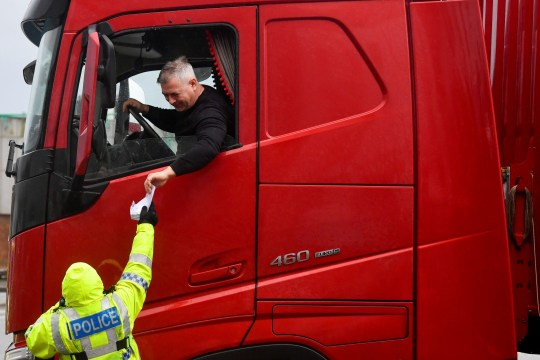 A police officer checks the documentation of a lorry driver upon his arrival to the Port of Dover,