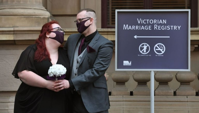 Anna and Ulf Crothers have their photo taken after marrying at the Victorian Marriage Registry in Melbourne on August 5, 2020, on the last day before weddings are banned in Melbourne for the next six weeks due to a new lockdown. - Australia's worst-hit state of Victoria reported 725 new cases and 15 coronavirus deaths on August 5, including a man in his 30s, making it the country's deadliest day of the pandemic to date. (Photo by William WEST / AFP) (Photo by WILLIAM WEST/AFP via Getty Images)