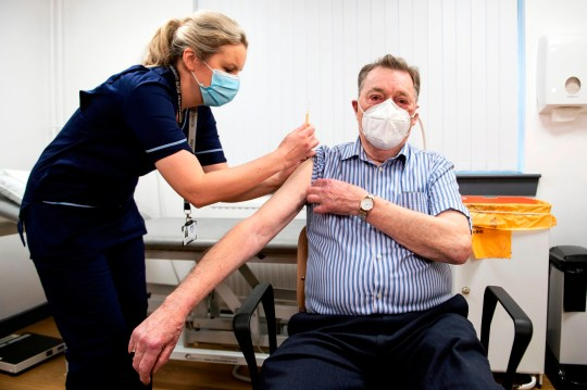 Advanced nurse practitioner Justine Williams (L) prepares to administer a dose of the AstraZeneca/Oxford Covid-19 vaccine to 82-year-old James Shaw, the first person in Scotland to receive the vaccination, at the Lochee Health Centre in Dundee on January 4, 2021. (Photo by Andy Buchanan / POOL / AFP) (Photo by ANDY BUCHANAN/POOL/AFP via Getty Images)