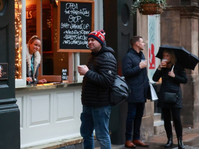 People drink outside a pub that is open for takeaway drinks, amid the coronavirus disease (COVID-19) outbreak, in London, Britain December 16, 2020. REUTERS/Hannah Mckay