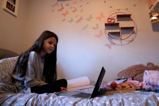 Milly, 8, takes part in an online school lesson from home as the country starts a lockdown, in Hertford, Britain, January 6, 2021. REUTERS/Andrew Couldridge
