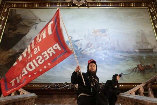 WASHINGTON, DC - JANUARY 06: A protester holds a Trump flag inside the US Capitol Building near the Senate Chamber on January 06, 2021 in Washington, DC. Congress held a joint session today to ratify President-elect Joe Biden's 306-232 Electoral College win over President Donald Trump. A group of Republican senators said they would reject the Electoral College votes of several states unless Congress appointed a commission to audit the election results. (Photo by Win McNamee/Getty Images)