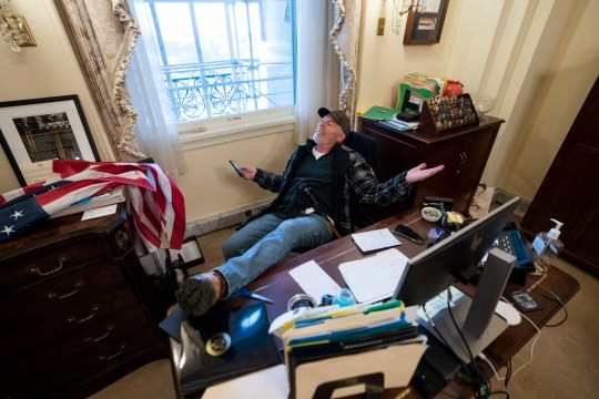 Richard 'Bigo' Barnett / A supporter of US President Donald J. Trump sits on the desk of US House Speaker Nancy Pelosi, after supporters of US President Donald J. Trump breached the US Capitol security in Washington, DC, USA, 06 January 2021. Protesters stormed the US Capitol where the Electoral College vote certification for President-elect Joe Biden took place. EPA/JIM LO SCALZO