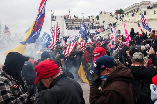 Les partisans du président américain Donald Trump réagissent aux gaz lacrymogènes lors d'un affrontement avec des policiers devant le Capitole américain à Washington, États-Unis, le 6 janvier 2021. REUTERS / Leah Millis