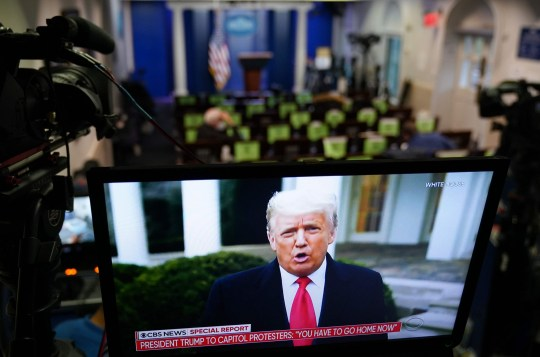 US President Donald Trump is seen on TV from a video message released on Twitter, seen in an empty Brady Briefing Room at the White House in Washington, DC on January 6, 2020. - Thousands of Trump supporters, fueled by his spurious claims of voter fraud, flooded the nation's capital protesting the expected certification of Joe Biden's White House victory by the US Congress. (Photo by MANDEL NGAN / AFP) (Photo by MANDEL NGAN/AFP via Getty Images)