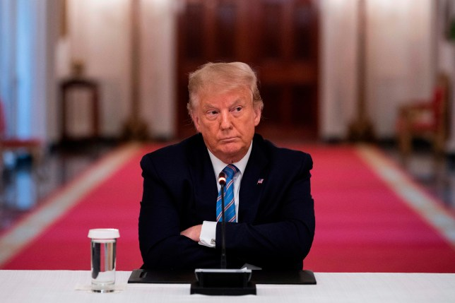 US President Donald Trump sits with his arms crossed