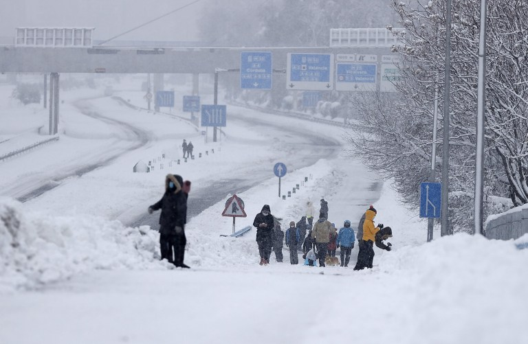 MADRID, SPAIN - JANUARY 09: People walk on snow covered M-30 highway after its closure due to snow during heavy snowfall in Madrid, Spain on January 09, 2021. Spain is on red alert for a second day due to storm Filomena, which has brought unusually cold weather and heavy snowfalls. The storm has caused cancelled services and transport disruption. (Photo by Burak Akbulut/Anadolu Agency via Getty Images)