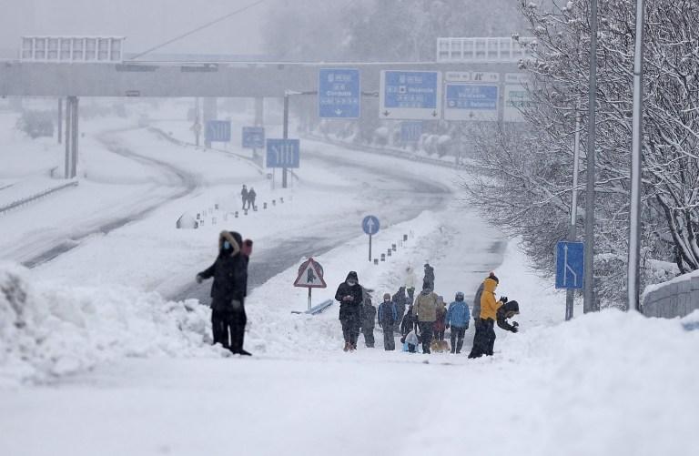 MADRID, ESPAGNE - 09 JANVIER: Les gens marchent sur l'autoroute M-30 couverte de neige après sa fermeture en raison de la neige lors de fortes chutes de neige à Madrid, Espagne le 09 janvier 2021. L'Espagne est en alerte rouge pour un deuxième jour en raison de la tempête Filomena, qui a apporté un temps exceptionnellement froid et de fortes chutes de neige.  La tempête a causé des services annulés et des perturbations des transports.  (Photo par Burak Akbulut / Agence Anadolu via Getty Images)
