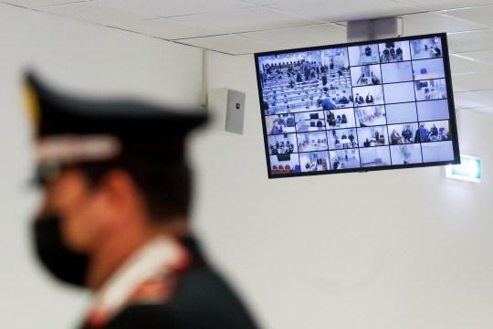 Certains des accusés dans un procès contre 355 membres présumés de la mafia 'Ndrangheta, accusés d'un ensemble d'accusations, sont vus sur un écran alors qu'ils se joignent via un lien vidéo le premier jour de leur procès,