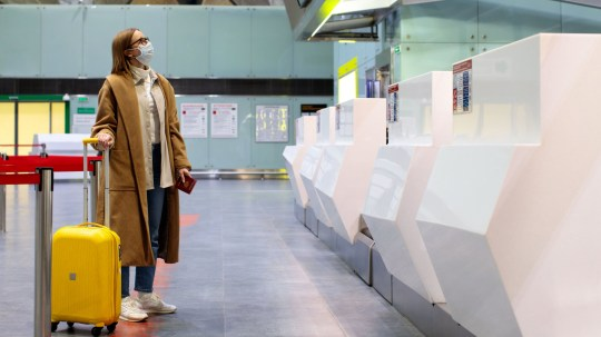 Woman with luggage stands at almost empty check-in counters at the airport terminal