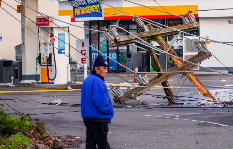 A broken utility poles rests in a Shell gas station a block south of Myrtle on Ellis Avenue South in Seattle, Wednesday, Jan. 13, 2021, following an overnight storm. (Mike Siegel/The Seattle Times via AP)