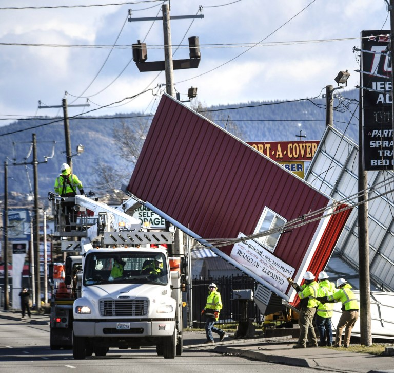 Crews work to free a carport blown into power and cable lines in Spokane Valley, Wash., after high winds hit the area, Wednesday, Jan. 13, 2021. (Dan Pelle/The Spokesman-Review via AP)