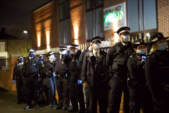 Met officers in masks lined up. Police tried to disperse 'travellers' who allegedly flouted coronavirus rules and gathered for a wake at a caravan park in Seven Sisters, London.