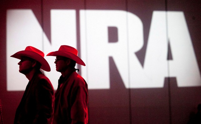 Two men in cowboy hats walking past an NRA sign. The NRA has filed for bankruptcy and announced it is moving from New York to Texas.