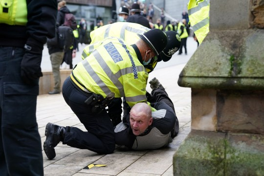 Police restraining an anti-lockdown protester on the floor. Brits have ignored Boris Johnson's pleas to stay at home this weekend.