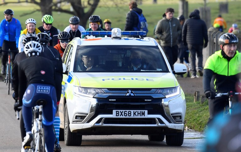 A police car patrols as people take permitted exercise, during current lockdown restrictions, amid the spread of the coronavirus disease (COVID-19) pandemic, in Richmond Park, London, Britain, January 17, 2021. REUTERS/Toby Melville