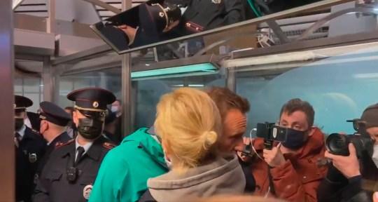 Le chef de l'opposition russe et militant anti-corruption Alexei Navalny et son épouse Yulia (tous deux au centre), lors de la détention de Navalny par des officiers