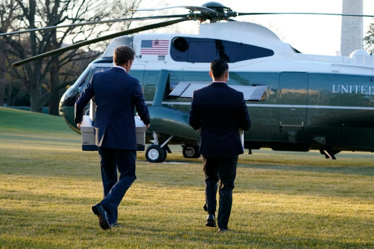 White house staff carry boxes to Marine One helicopter