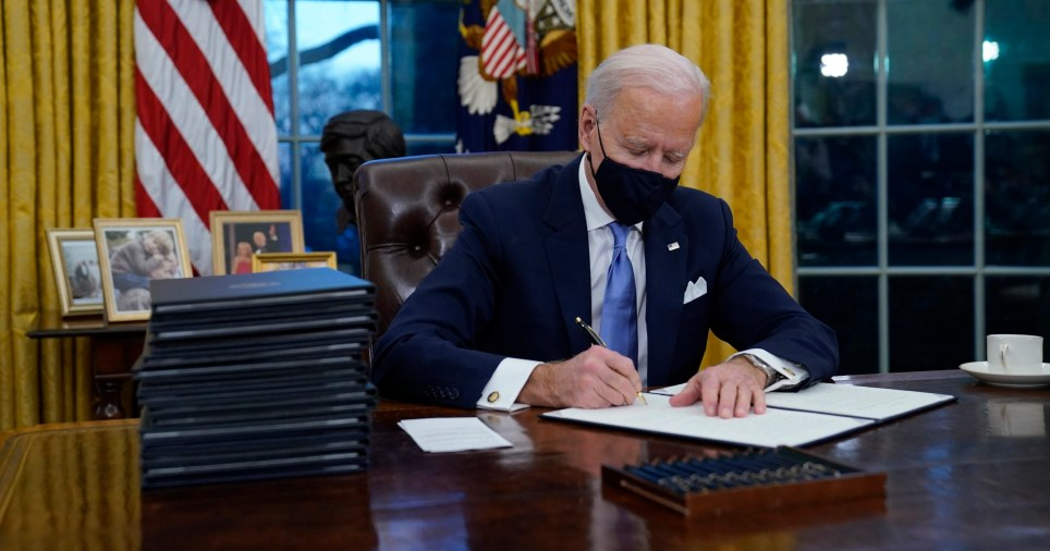 President Joe Biden signs his first executive orders in the Oval Office of the White House on Wednesday, Jan. 20, 2021, in Washington.??(AP Photo/Evan Vucci)