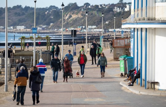 People walk along the sea front on Bournemouth beach in Dorset, during England's third national lockdown to curb the spread of coronavirus. Picture date: Saturday January 23, 2021. PA Photo. See PA story HEALTH Coronavirus. Photo credit should read: Andrew Matthews/PA Wire