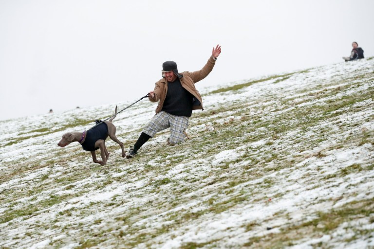 A man plays with a dog in the snow in Campbell Park, in Milton Keynes, Britain January 24, 2021. REUTERS/Andrew Boyers