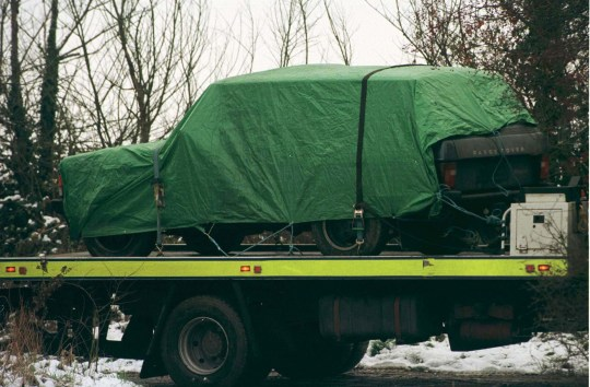 Police remove the Range Rover car, in which three bodies were found by a farmer on the back of low loader. The three men, aged 20-40, who died of gunshot wounds after being blasted in the head at point-blank range by a shotgun, were discovered in the car parked on a tree-lined track just 300 yards from the busy A130 Chelmsford to Southend road at Rettendon, Essex. Two ruthless gunmen Michael Steele, 55, and Jack Whomes, 36 were found guilty of executing three drug barons in the lane after an underworld row. The pair are being sentenced at the Old Bailey later.