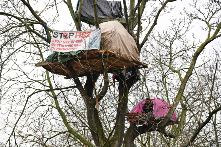 Activists sit in tree houses at their protest camp against the HS2 hi-speed rail line, near Euston train station in central London on January 27, 2021. - Designed to run to the former industrial powerhouse Birmingham and then Manchester and Leeds, HS2 was supposed to follow on from London's southern Eurostar connection with Paris. But it has done little but accrue costs since first being formally proposed more than a decade ago.