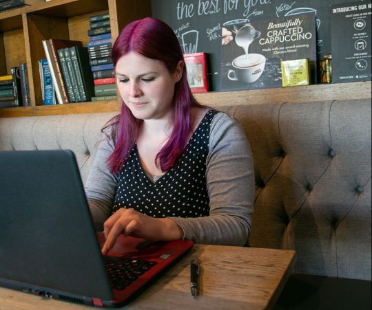 Purple-haired author sits in cafe typing on laptop